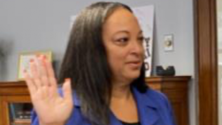 A black woman in a blue jacket with one hand raised to be sworn in.