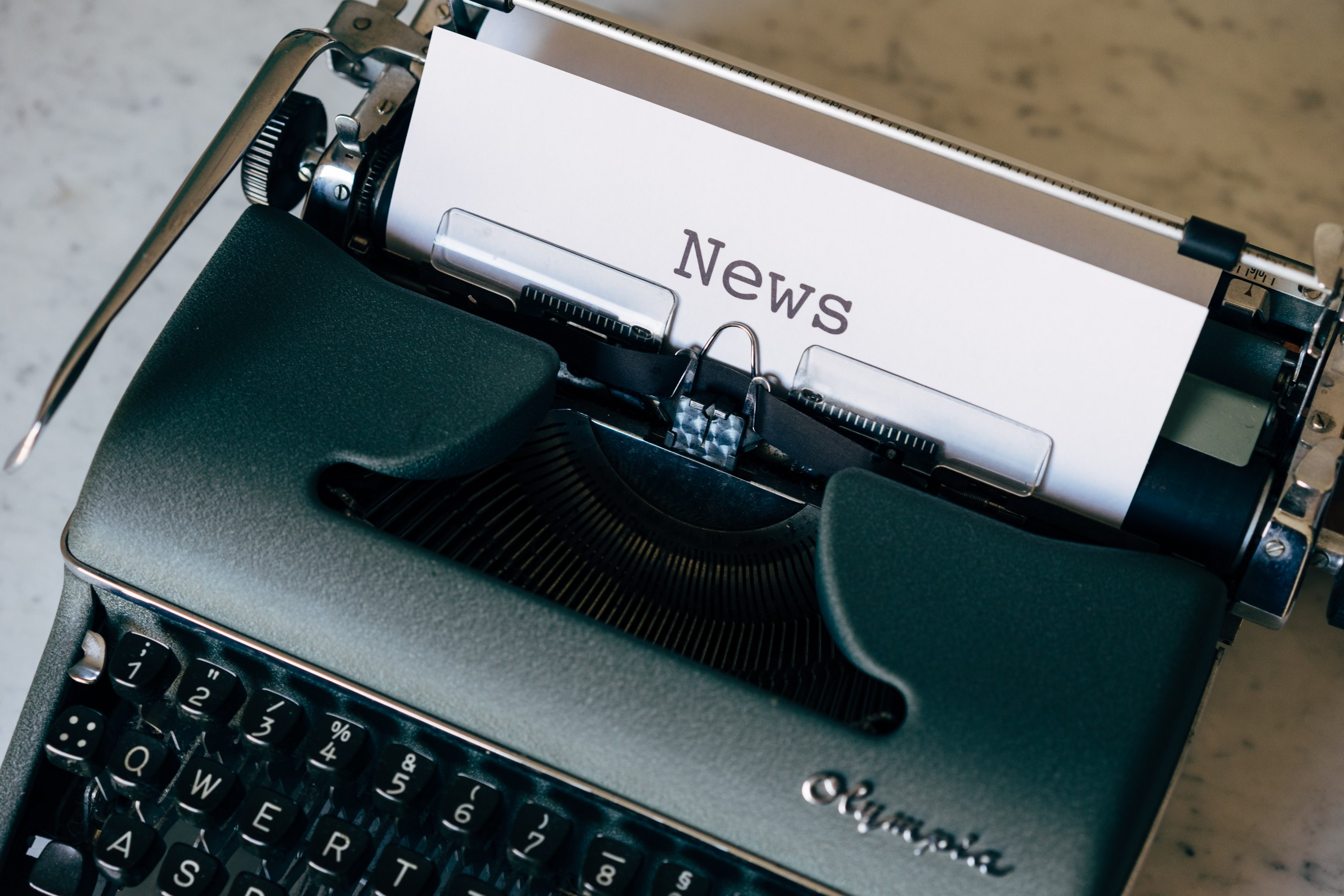 A typewriter with a page labeled News